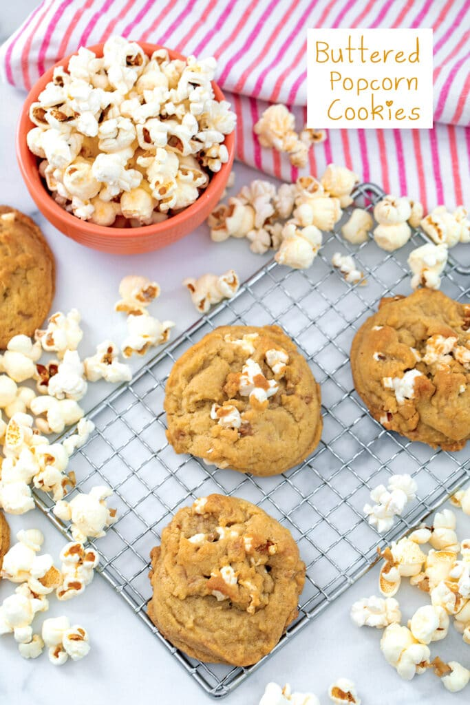 Buttered popcorn cookies on a metal rack with popcorn all around and recipe title at top