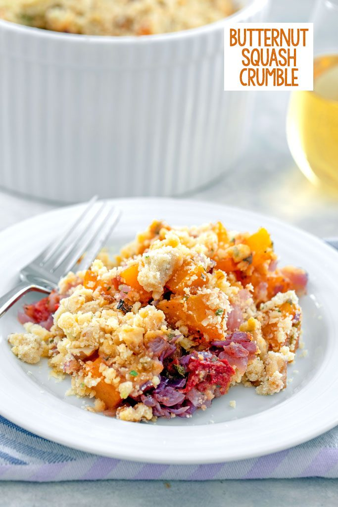 Head-on view of a white plate with butternut squash crumble with a fork and casserole dish in the background with recipe title at top
