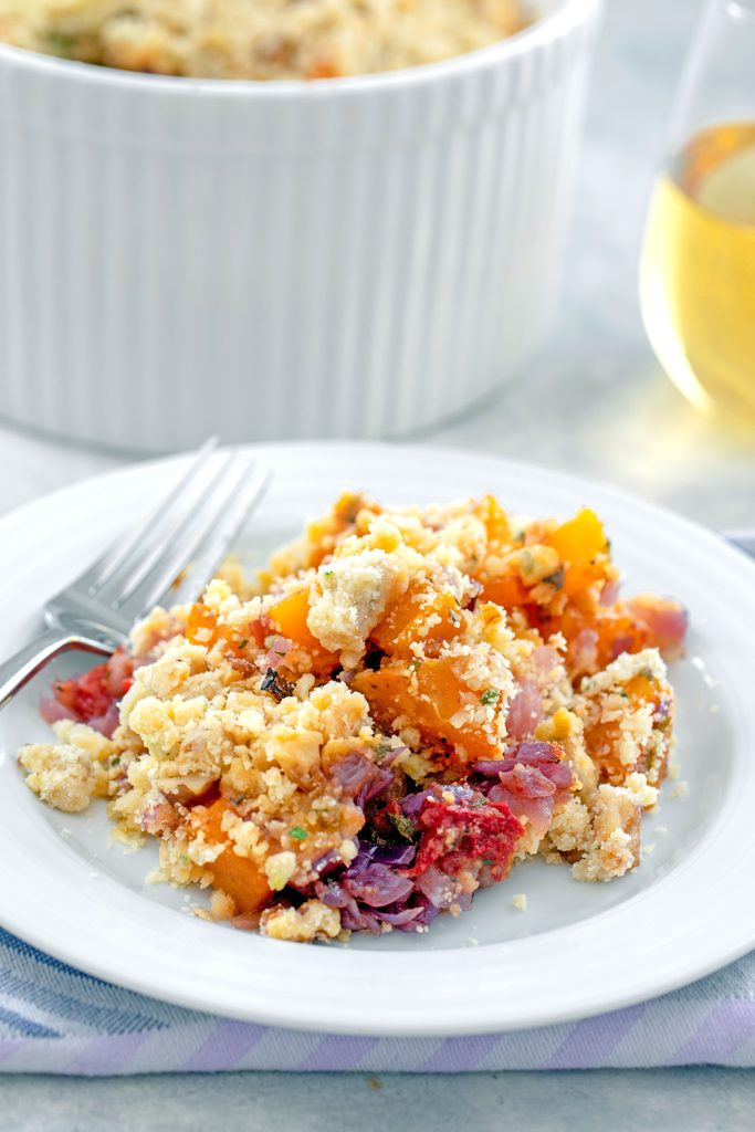 Head-on view of a white plate with butternut squash crumble with a fork and casserole dish in the background