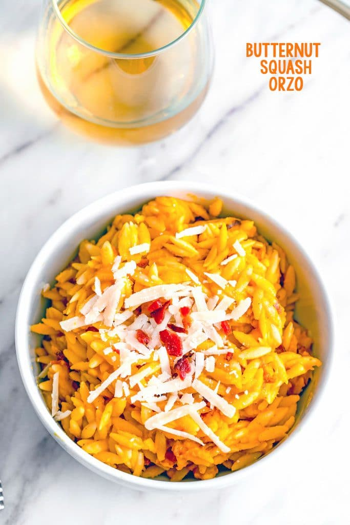 Overhead view of bowl of butternut squash orzo with grated parmesan and crumbled bacon on marble surface with glass of wine in the background and recipe title at top