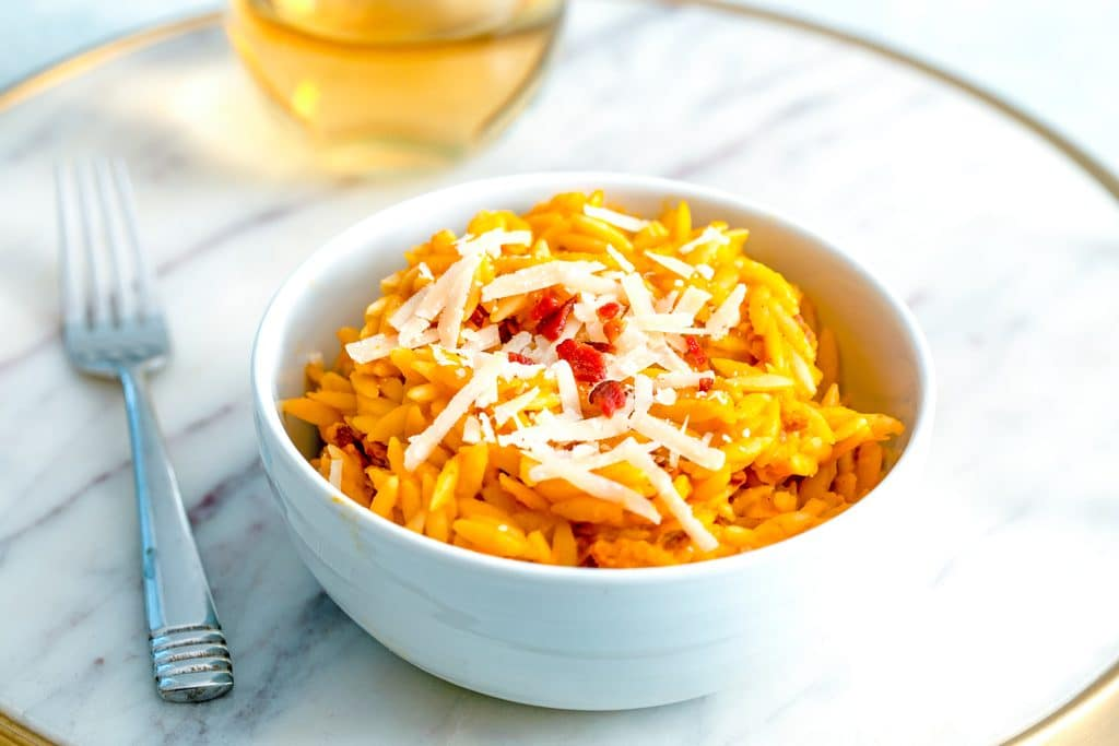 Head-on close up view of butternut squash orzo topped with parmesan cheese and crumbled bacon in a white bowl with fork and glass of white wine in background