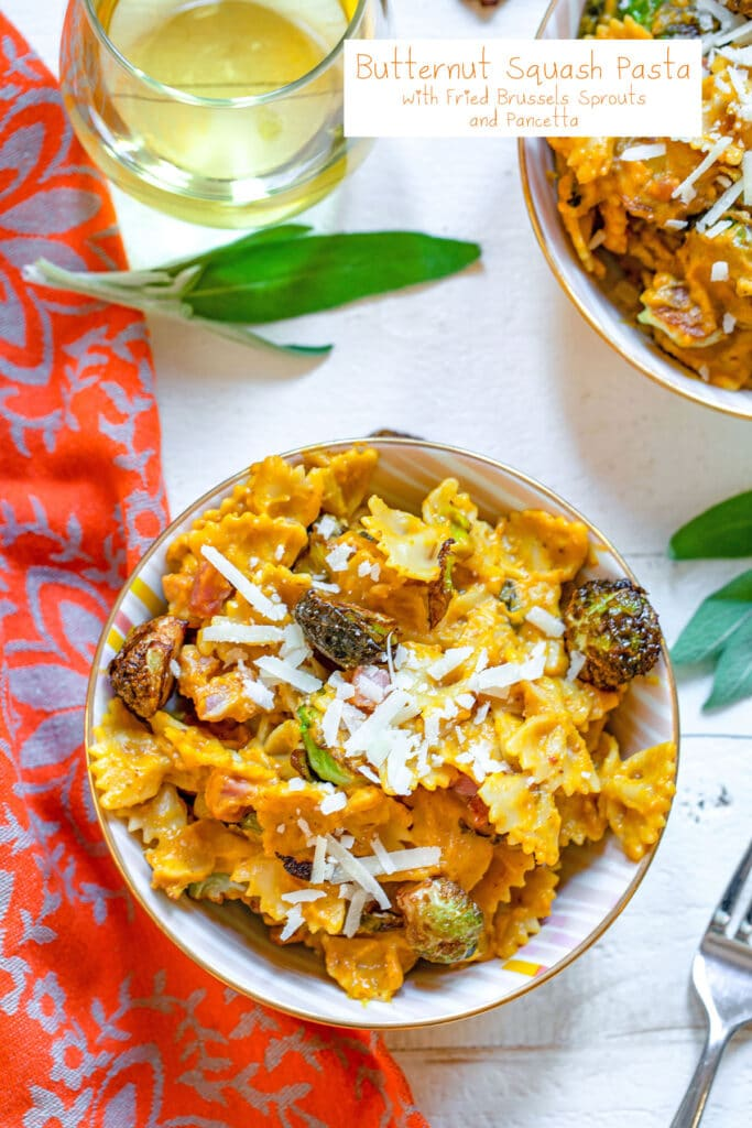 Overhead view of butternut squash pasta with fried brussels sprouts, pancetta, and parmesan cheese with sage, drinking glass, and second bowl of pasta in background and recipe title at top