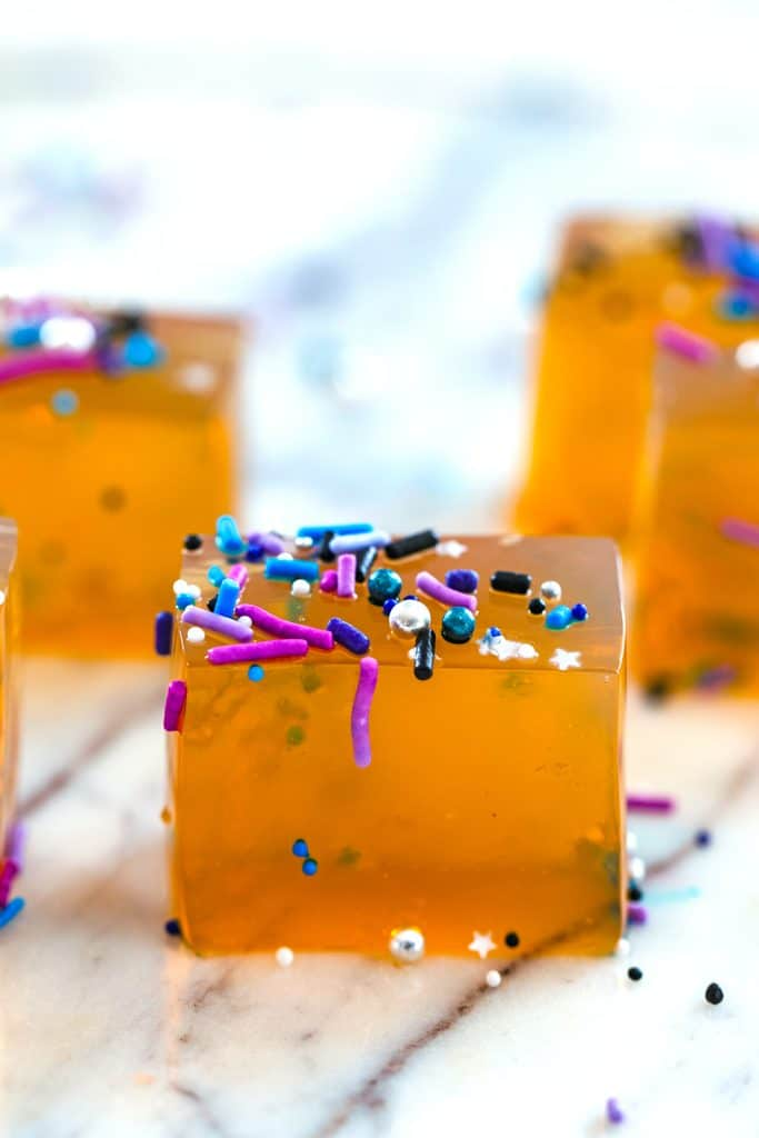 Head-on view of butterscotch jello shots cut into cubes and covered with pretty sprinkles