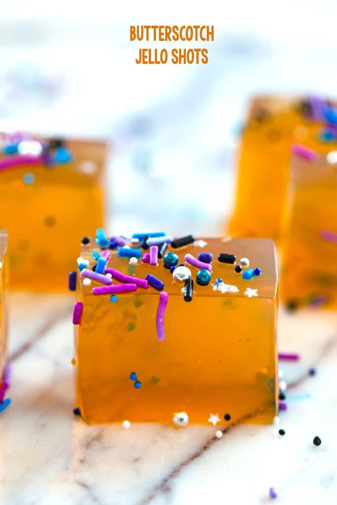 "Head-on view of butterscotch jello shots cut into cubes and covered with pretty sprinkles with ""Butterscotch Jello Shots"" at top of image"