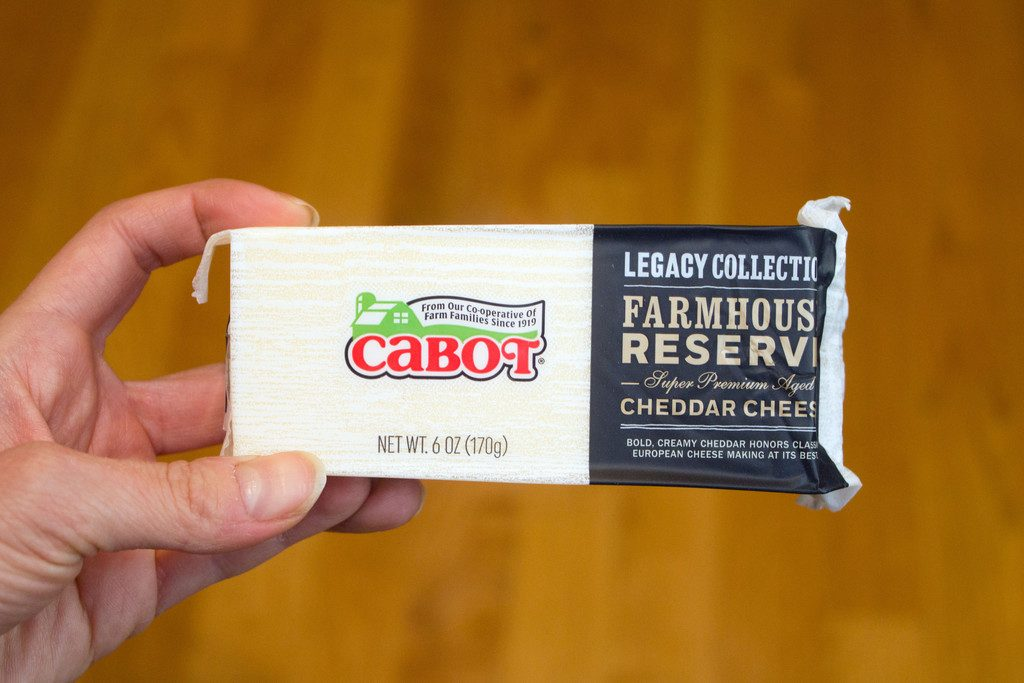 Hand holding a block of Cabot Farmhouse Reserve Cheddar Cheese