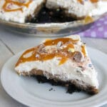 View of a slice of Cadbury Creme Egg Chocolate Cream Pie on a white plate with full pie in background