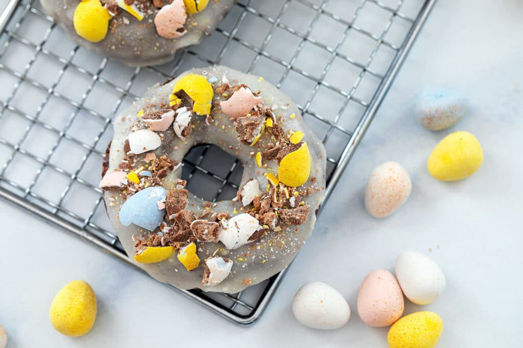 Landscape view of Cadbury Mini Egg donut on a baking rack surrounded by more Mini Eggs