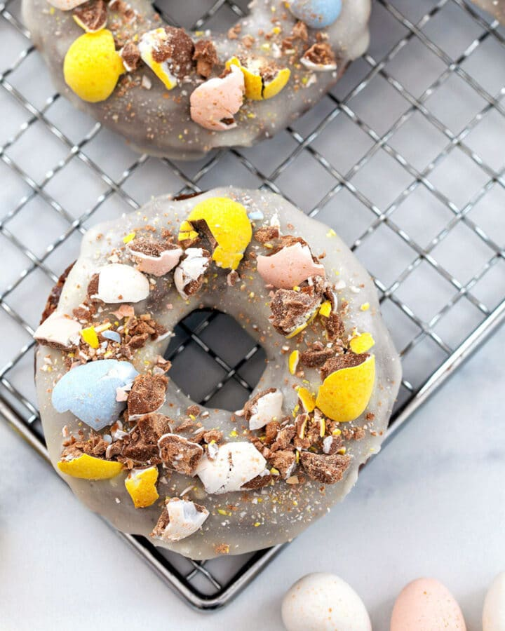 Overhead view of a chocolate Cadbury Mini Egg donut with vanilla icing and crushed Cadbury Mini Eggs on top and more mini eggs all around
