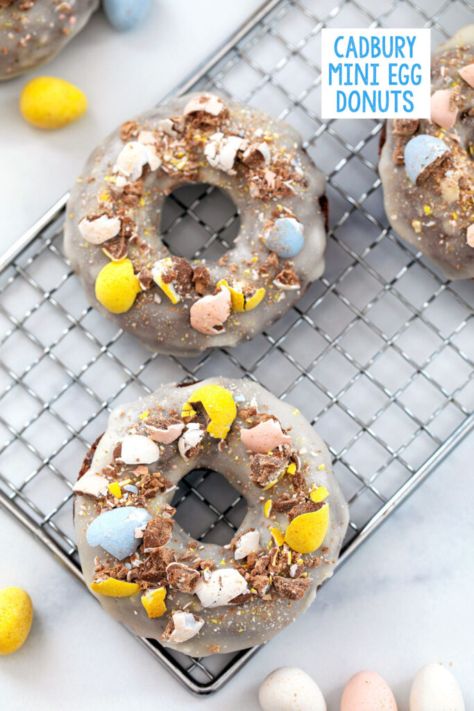 Overhead view of three Cadbury Mini Egg donut topped with crushed Cadbury Mini Eggs on wire rack with recipe title at top