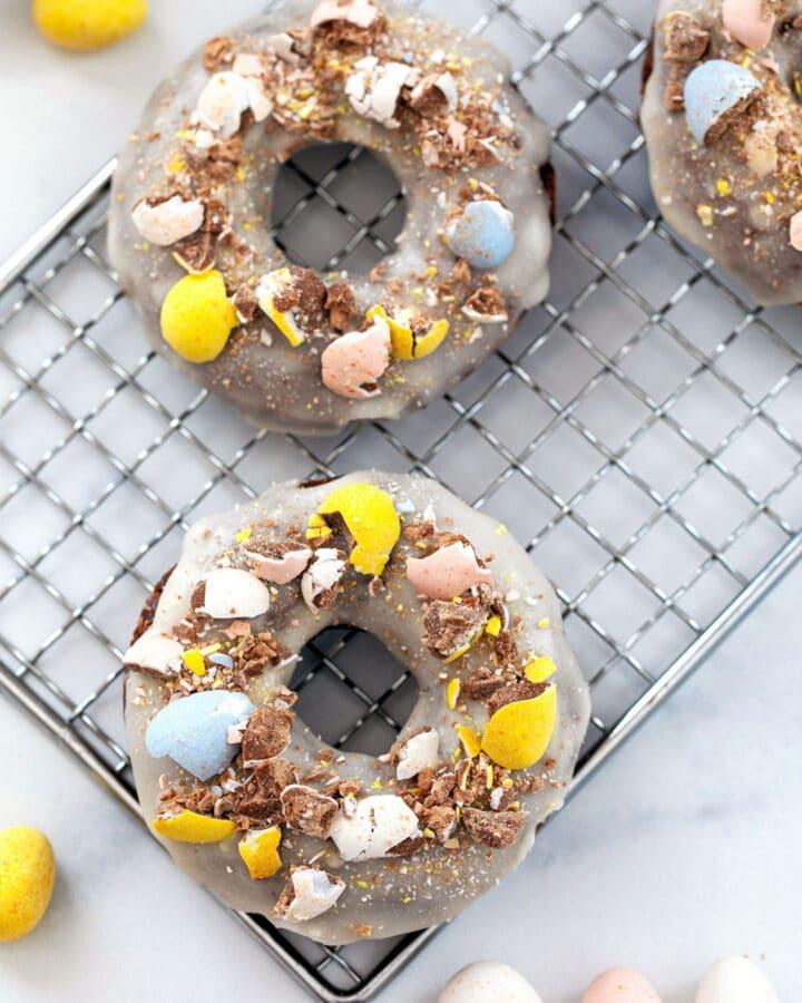 Three Cadbury Mini Egg donuts on a metal baking sheet with Cadbury Mini Eggs all around