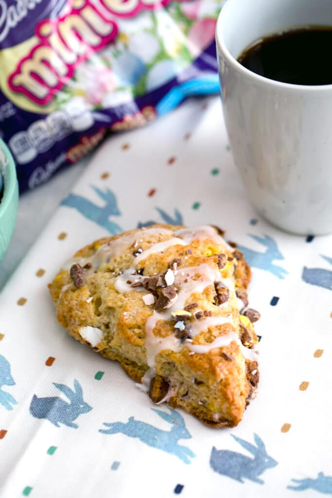 Overhead view from a distance of Cadbury Mini Egg scone on a bunny towel with bag of mini eggs and cup of coffee in the background