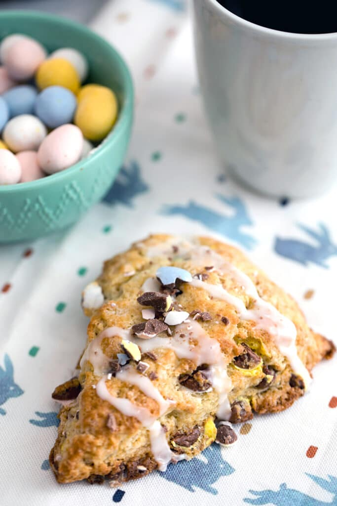 Overhead view of a Cadbury Mini Egg scone on a bunny towel with a bowl of mini eggs and a cup of coffee in the background and recipe title at top