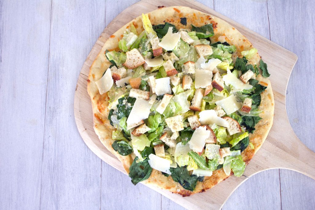 Overhead view of Caesar Salad Pizza on a pizza paddle