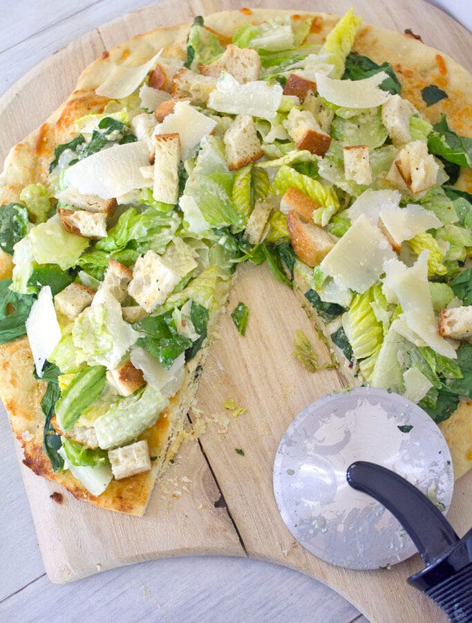 Caesar Salad Pizza -- This Caesar Salad Pizza combines pizza and salad with a thin crust parmesan dough, lots of cheese, spinach and romaine, and a creamy dressing   wearenotmartha.com
