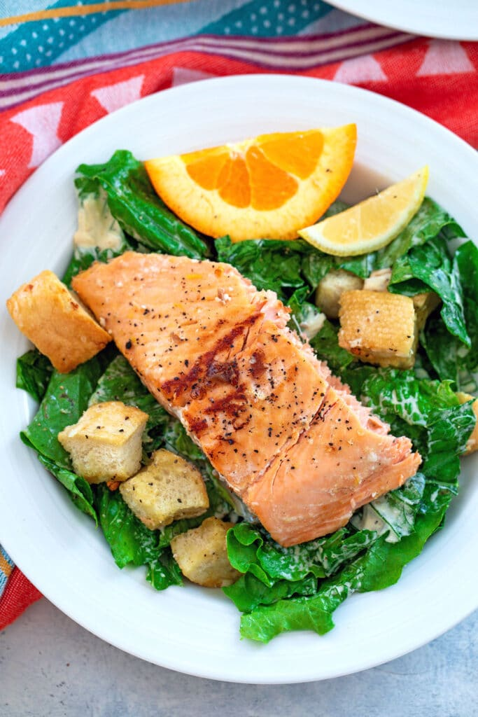 Closeup overhead view of a caesar salad topped with grilled citrus salmon and homemade croutons with orange and lemon wedge