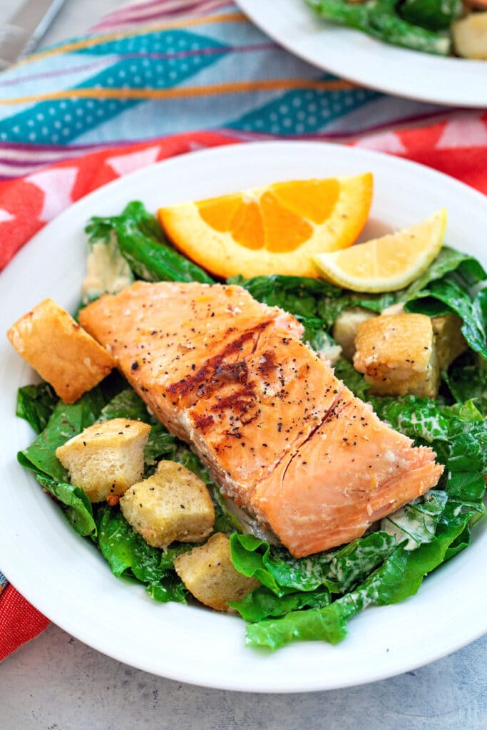 Head-on view of Caesar salad with croutons, orange and lemon wedges, and salmon on top