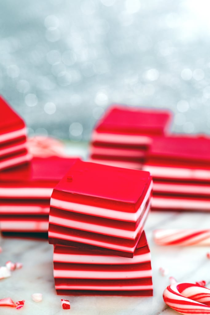 Head-on view of two red and white layered candy cane jello shots stacked on top of each other with crushed candy canes, mini candy canes, and more jello shots stacked in background.