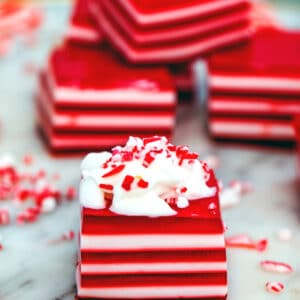 Head-on view of a red and white layered candy cane jello shot topped with whipped cream and crushed candy canes with more jello shots in the background