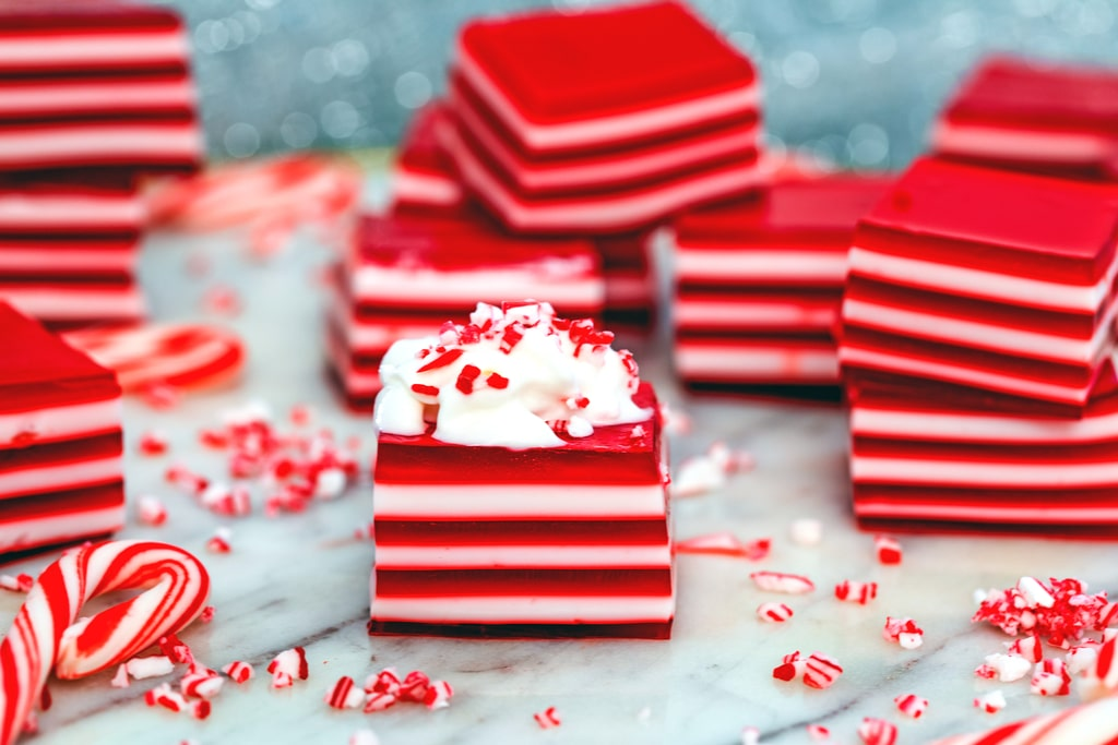 Landscape head-on view of multiple red and white layered candy cane jello shots, one with whipped cream on top with crushed candy canes and mini candy canes scattered around.