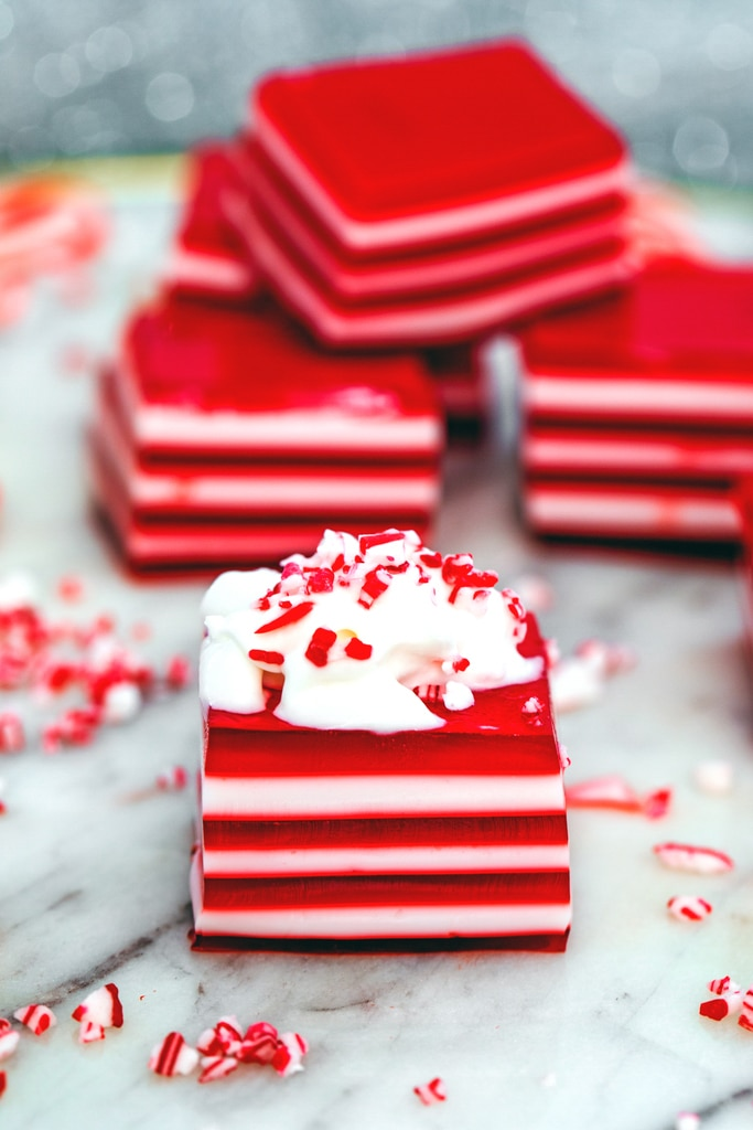 Head-on view of a red and white layered candy cane jello shot topped with whipped cream and crushed candy canes with more jello shots in the background.