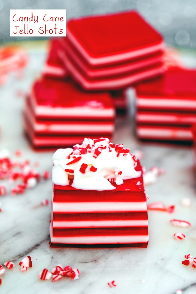 Head-on view of a red and white layered candy cane jello shot topped with whipped cream and crushed candy canes with stack of more jello shots in background and recipe title at top.