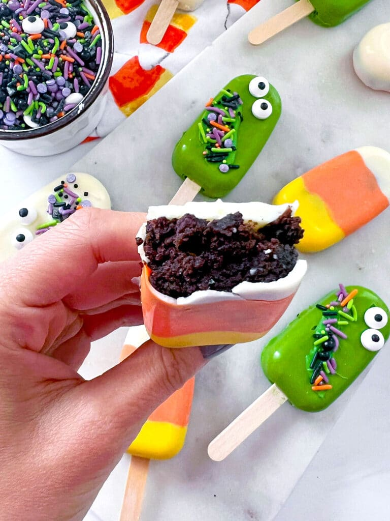 Overhead view of a candy corn cakesicle with a bite taken out of it showing chocolate cake in the middle