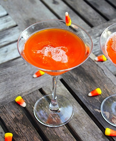 Overhead view of bright orange candy corn martini in glass on a wood table, surrounded by candy corn