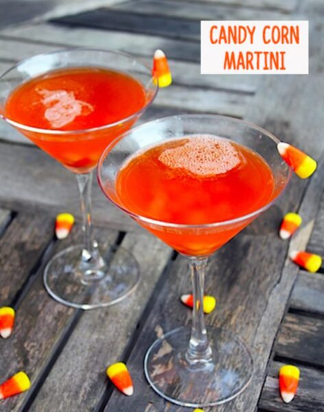 "Two martini glasses filled with bright orange candy corn vodka and butterscotch schnapps, surrounded by candy corn with ""Candy Corn Martini"" text at top"