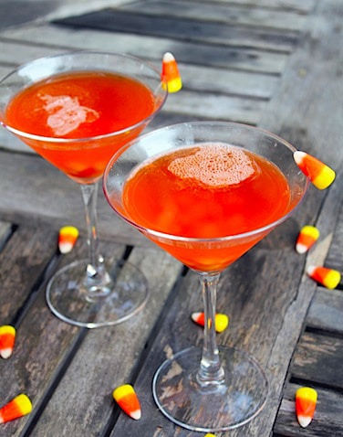 Two bright orange candy corn martinis on a wood table, surrounded by candy corn