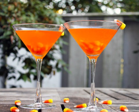 Head-on view of two bright orange candy corn martinis on a wooden table outside, surrounded by candy corn