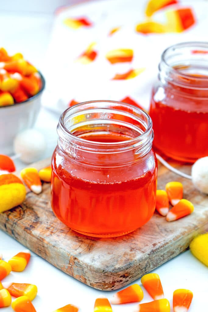 Overhead view of a small mason jar of candy corn simple syrup with candy corn all around