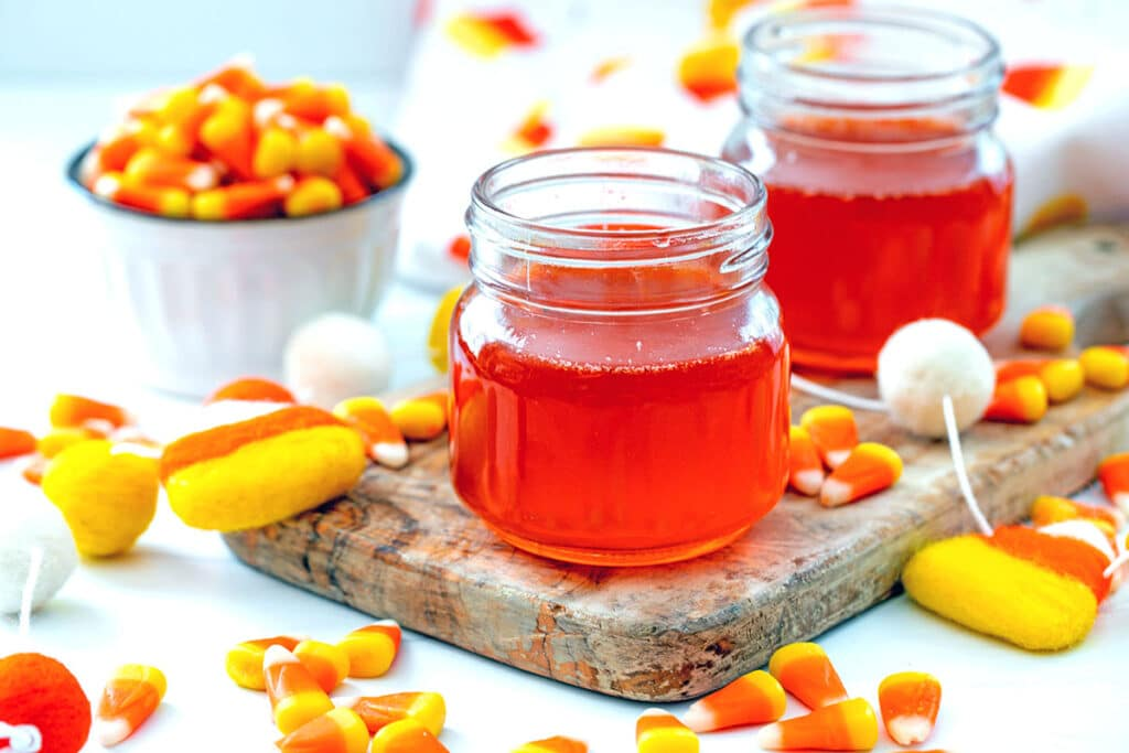 Landscape head-on view of two small jars of candy corn simple syrup with candy corn all around