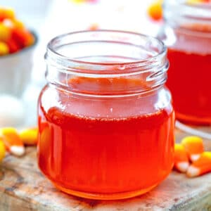 Up-close view of a small mason jar of bright orange candy corn simple syrup with candy corn all around