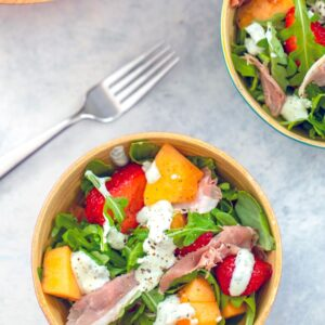 Cantaloupe and Prosciutto Arugula Salad with Mint Yogurt Dressing -- This easy to prepare Cantaloupe and Prosciutto Salad is packed with fresh ingredients, including strawberries, arugula, and goat cheese and is topped with a delicious mint yogurt dressing | wearenotmartha.com