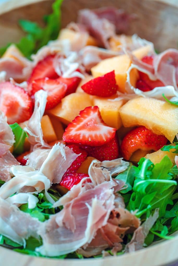 Closeup of large bowl with all salad ingredients, including arugula, strawberries, cantaloupe, and prosciutto