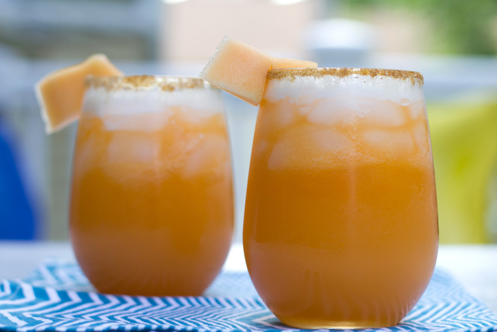 Landscape head-on view of two cantaloupe lime margaritas with cayenne salt rim and cantaloupe garnish