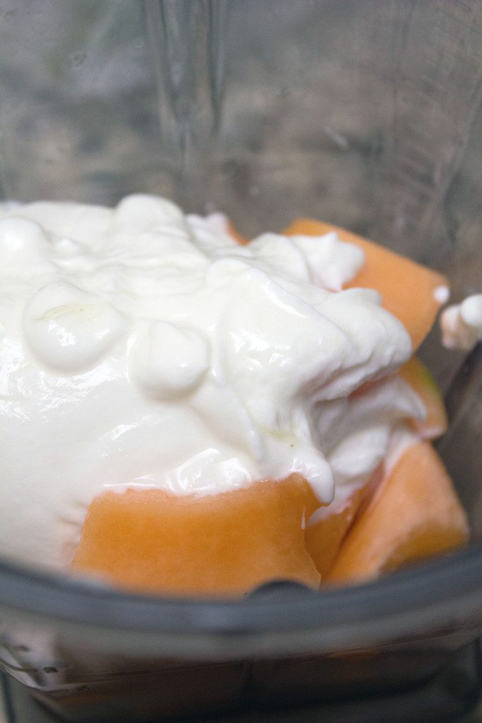 View of chopped cantaloupe and Greek yogurt in blender