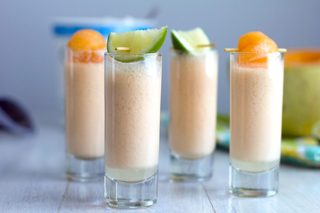 Landscape view of multiple cantaloupe boozy smoothie shooters with cantaloupe and lime garnishes