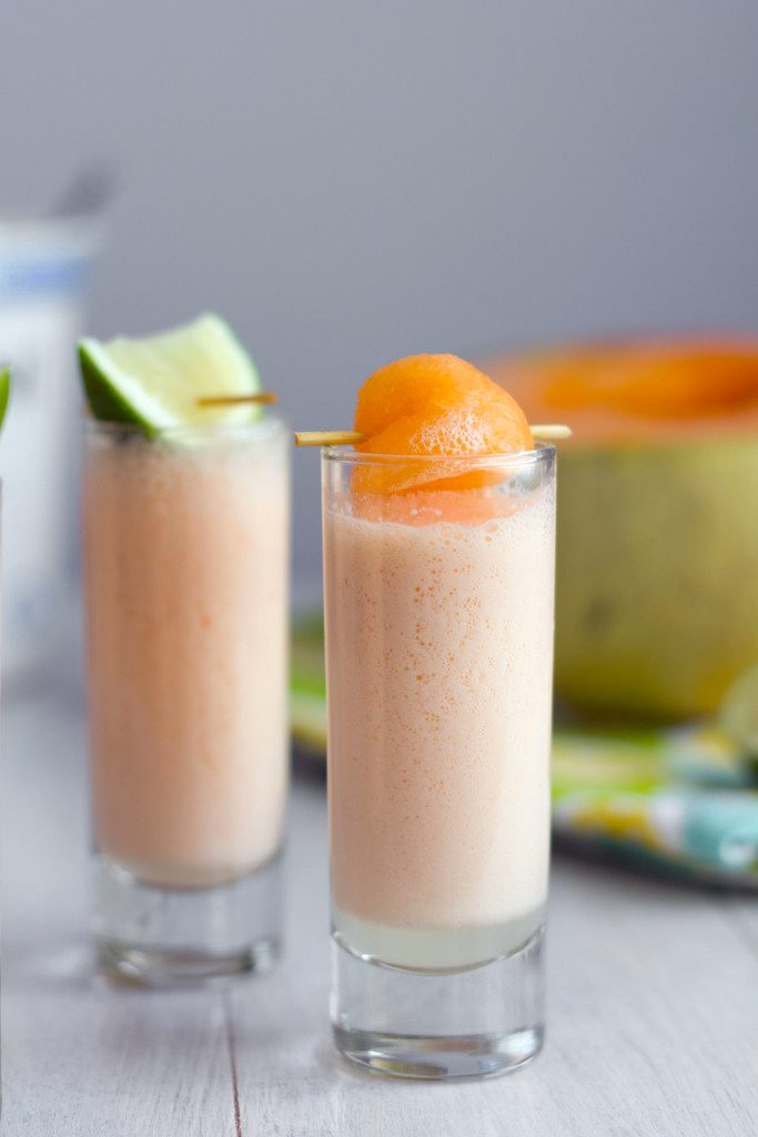 Head-on view of a cantaloupe boozy smoothie shooter with cantaloupe ball garnish with second smoothie with lime garnish and cantaloupe half in background
