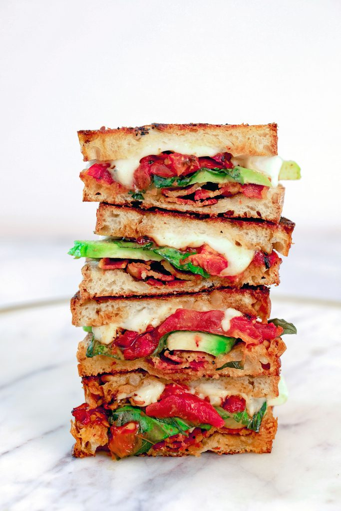 Head-on view of four halves of a caprese grilled cheese sandwich with avocado and bacon stacked on each other on a marble tray