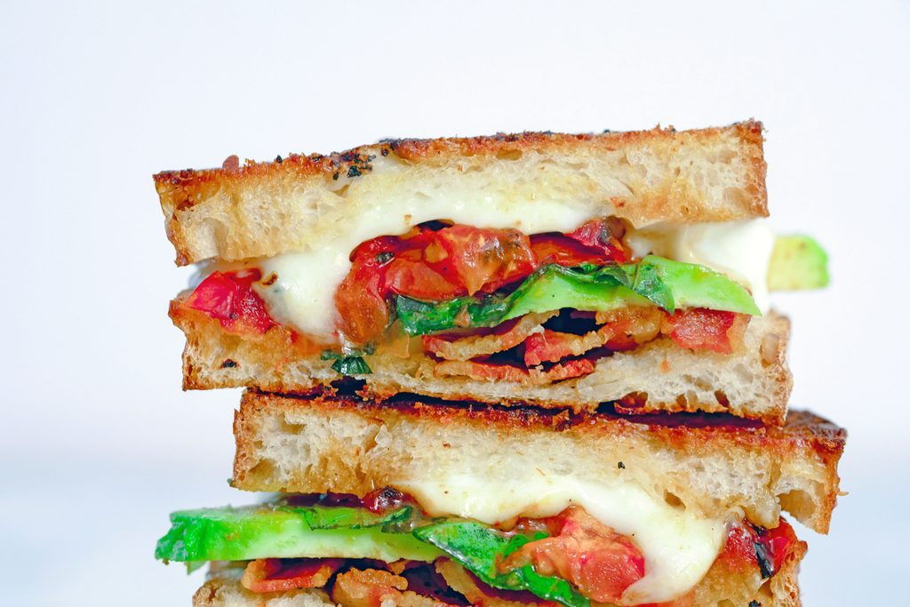 Landscape closeup head-on view of a half of a caprese grilled cheese sandwich with avocado and bacon stacked on top of other halves