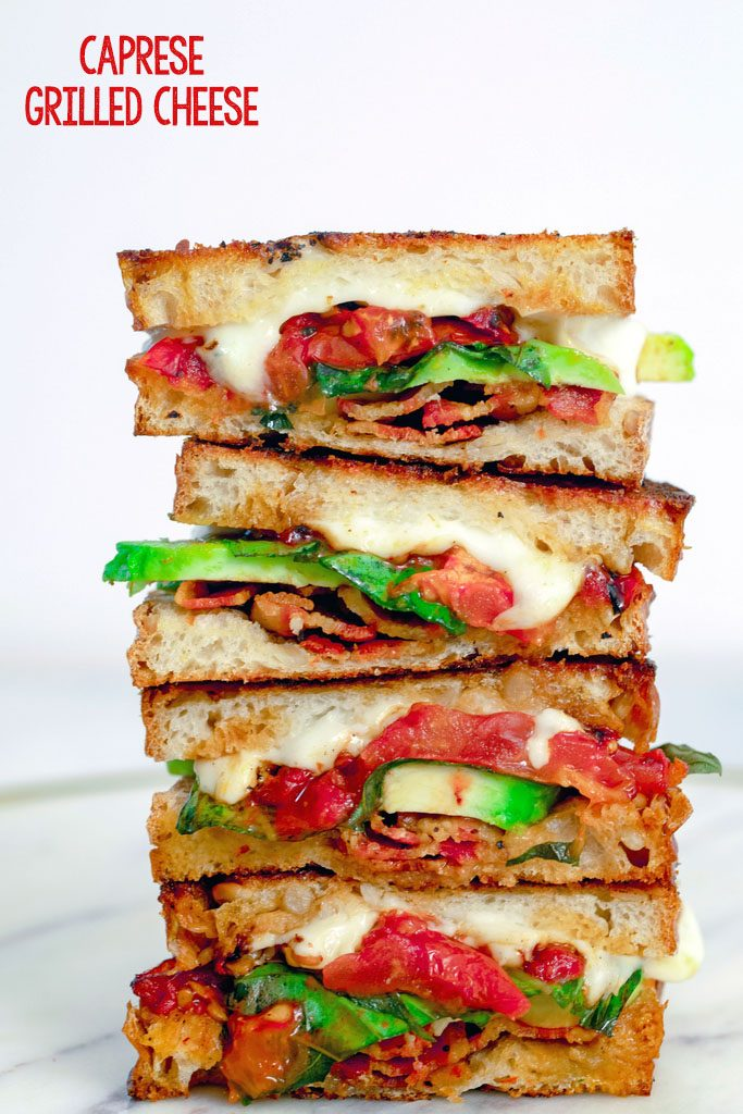 Head-on closeup view of four halves of a caprese grilled cheese sandwich with avocado and bacon all stacked on each other with recipe title at top