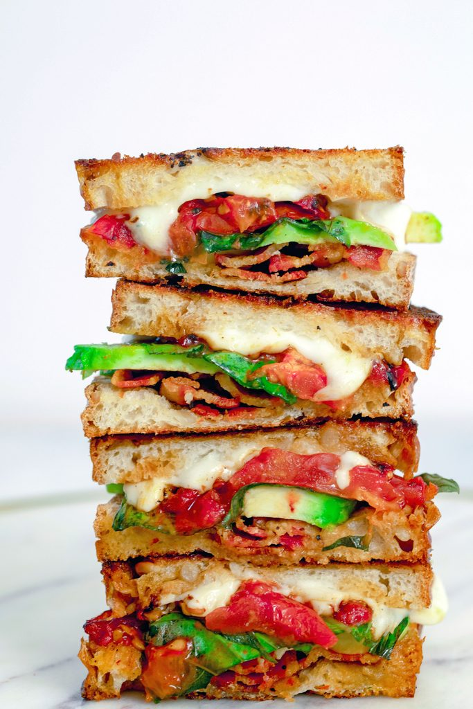 Head-on closeup view of four halves of a caprese grilled cheese sandwich with avocado and bacon all stacked on each other