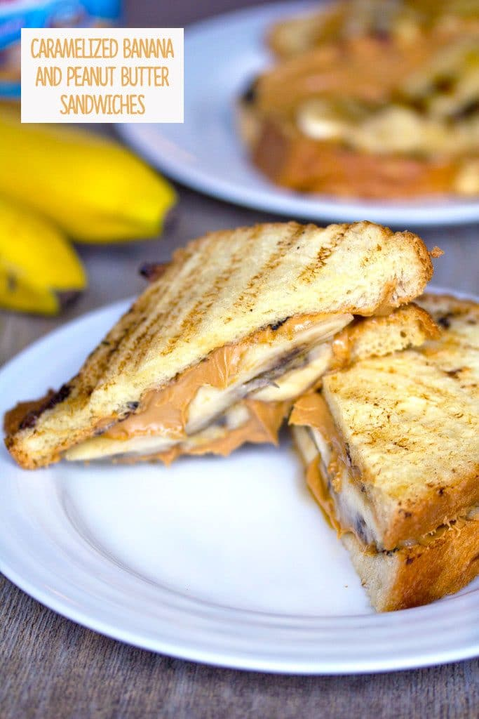 Head-on view of a caramelized banana and peanut butter sandwich cut in half on a white plate with a second sandwich, bananas, and peanut butter jar in the background and recipe title at the top