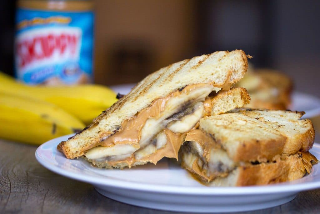 Landscape view of caramelized banana and peanut butter sandwich sliced in half on a white plate with bananas and peanut butter jar in background