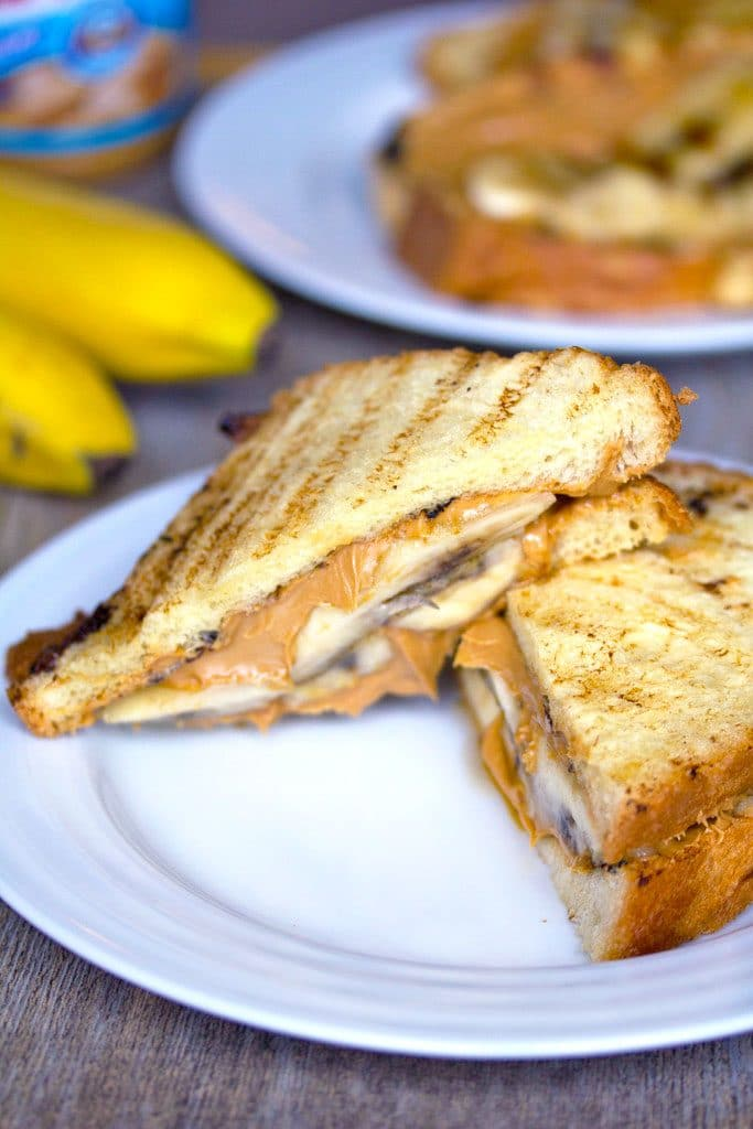 Head-on view of a caramelized banana and peanut butter sandwich cut in half on a white plate with a second sandwich, bananas, and peanut butter jar in the background