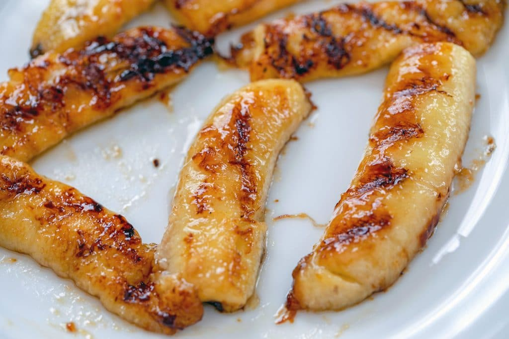 Overhead view of caramelized bananas on white plate