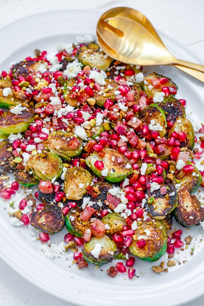 Overhead view of a white platter with caramelized brussels sprouts with pancetta, pomegranate, and feta with gold serving pieces