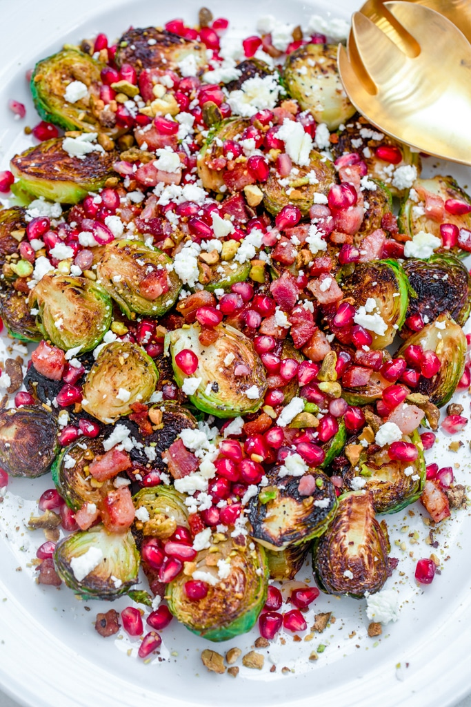 Overhead view of caramelized brussels sprouts with pancetta, pomegranate, and feta on a white platter with gold serving pieces