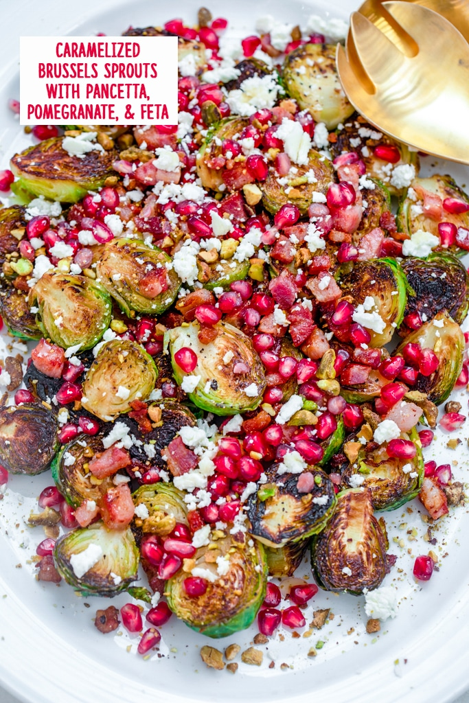 Overhead view of caramelized brussels sprouts with pancetta, pomegranate, and feta on a white platter with gold serving pieces and recipe title at top